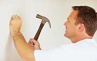 worker hammering nail into wall